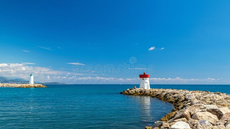 在入口的两座灯塔对法国海滨的海湾在反对一天空蔚蓝的一清楚的好日子与云彩 免版税库存图片