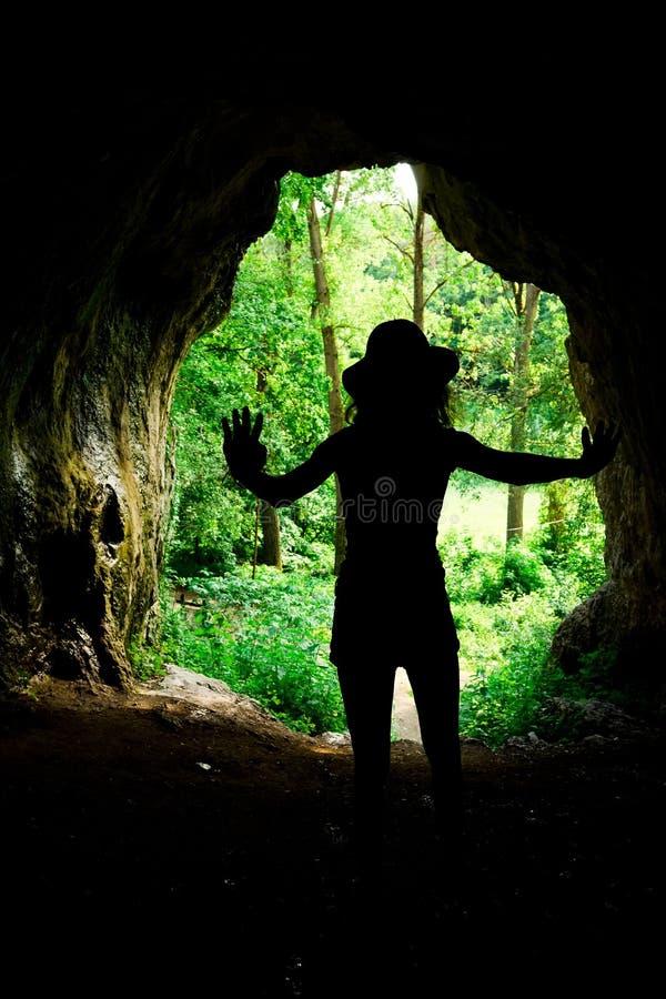 在入口的亭亭玉立的女孩剪影对在forrest的自然洞 免版税库存照片