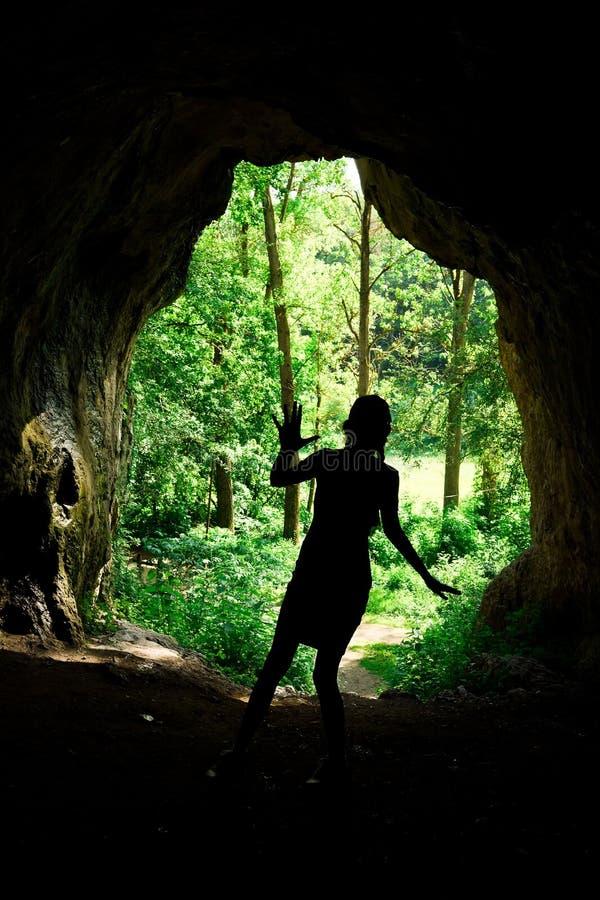 在入口的女孩的剪影对在forrest的自然洞 免版税库存图片