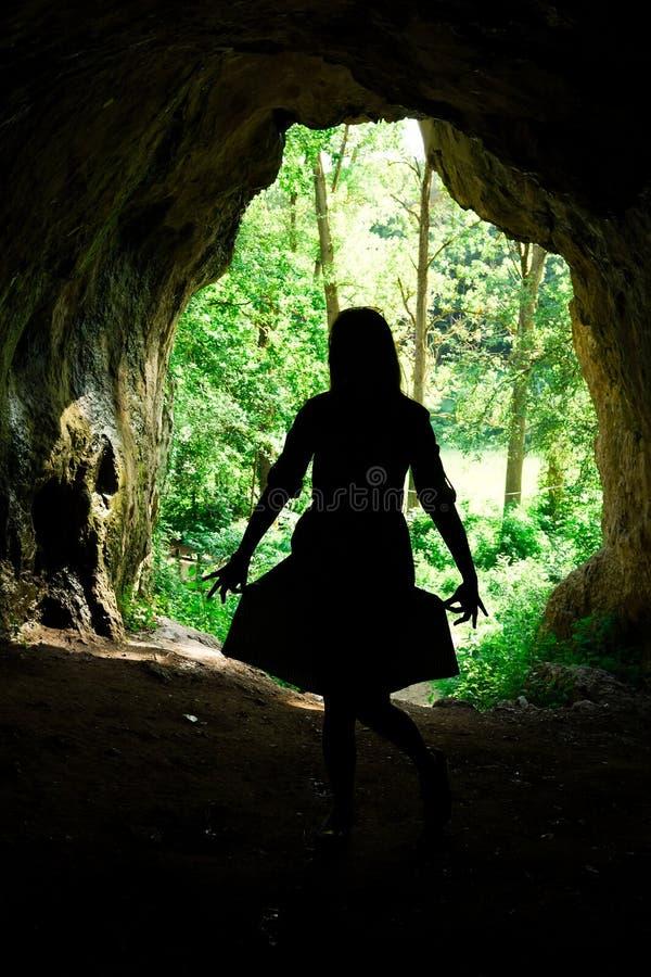 在入口的妇女的剪影对在forrest的自然洞 库存照片