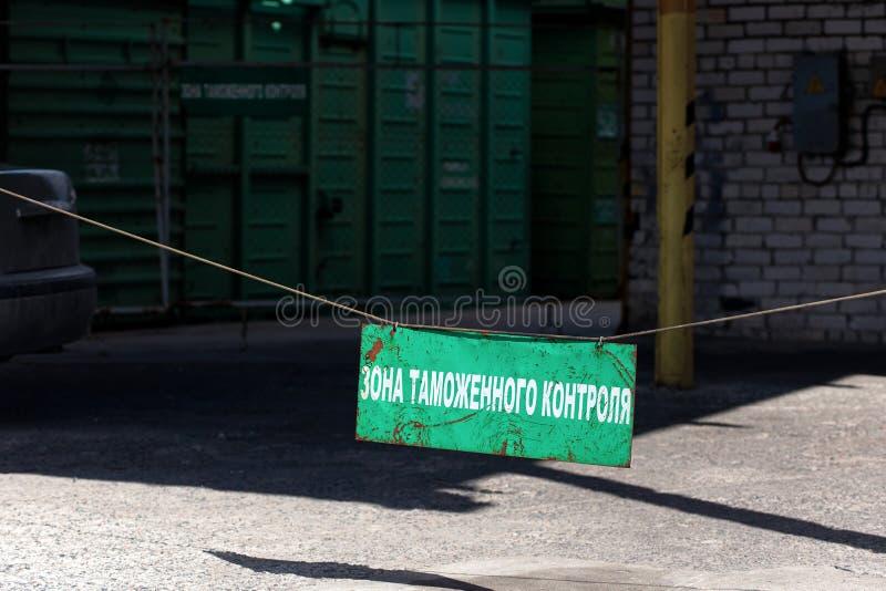 在入口的绿色老生锈的关税豁免区标志对与题字的出口结关用有货物铁路车的俄语在 库存照片