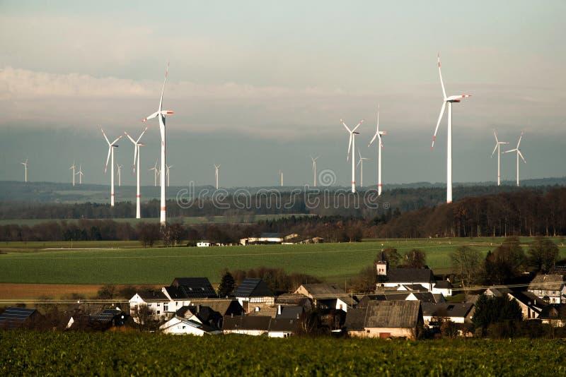 在全景视图前面的村庄在风力场风景在有白色发电器涡轮的德国 免版税库存图片