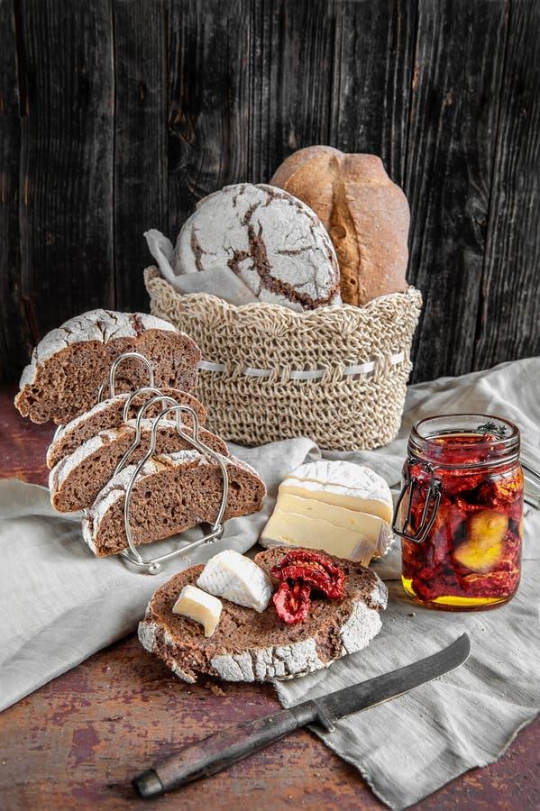 在全麦被发酵的手工制造乳酪和各式各样的蕃茄上添面包 免版税库存图片