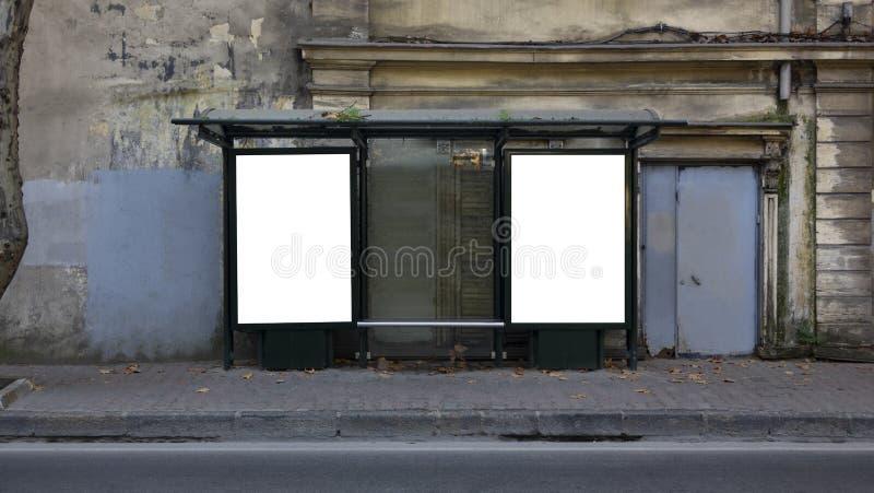 在公交车站的两个垂直的空白的白色广告牌在老城市街道上 图库摄影