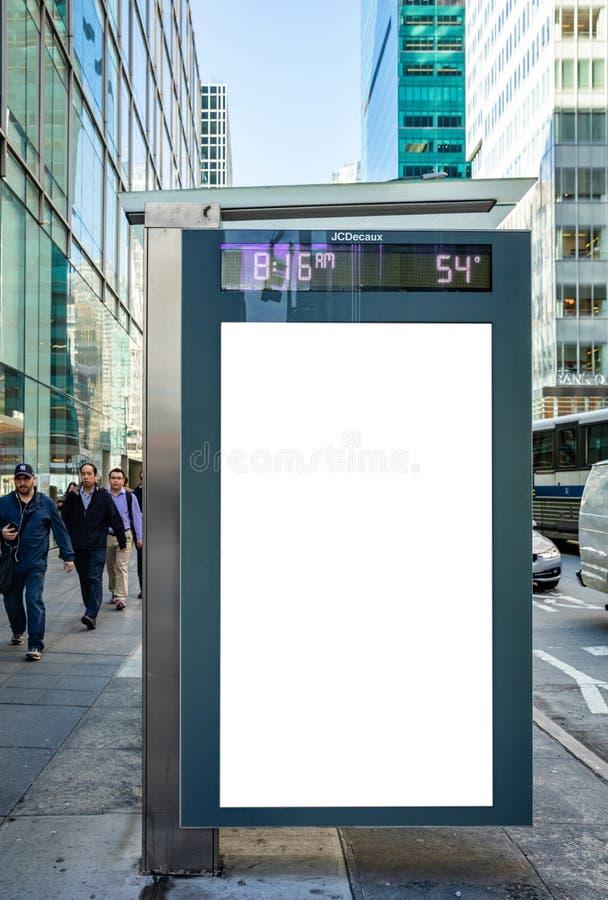 在公交车站的空白的广告牌做广告,纽约大厦和街道背景的 免版税库存照片