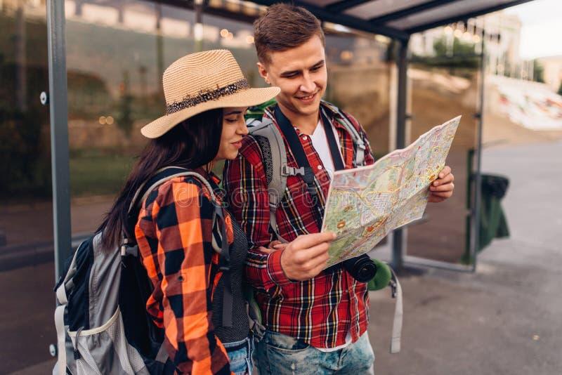 在公共汽车站的夫妇学习城市吸引力地图  免版税库存照片