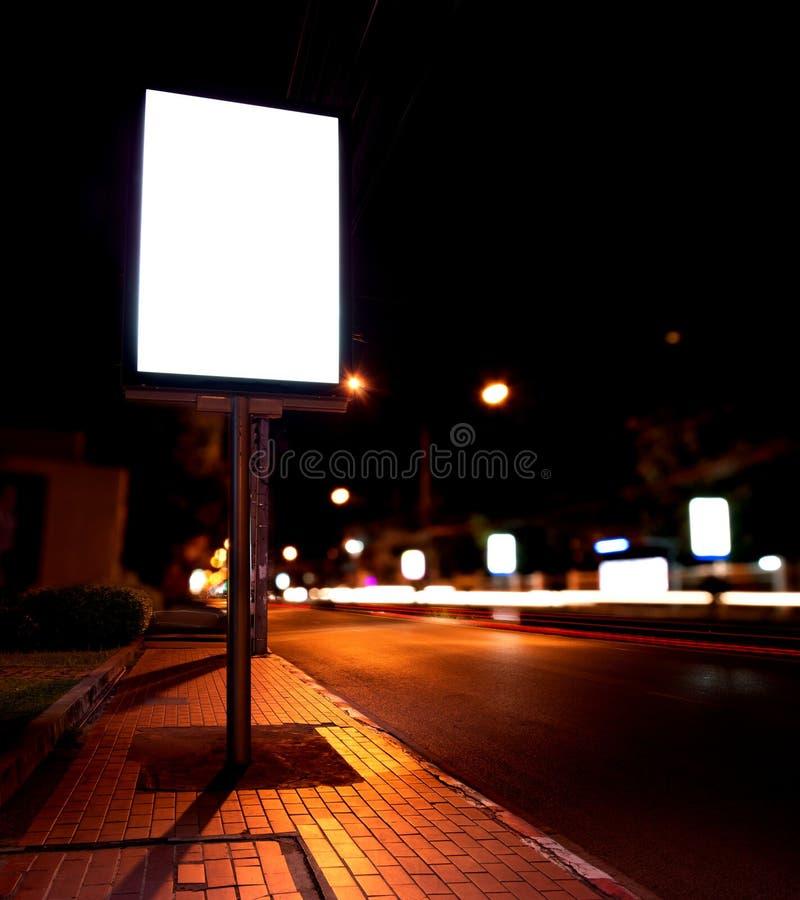 在公共汽车站的广告牌在夜 库存图片