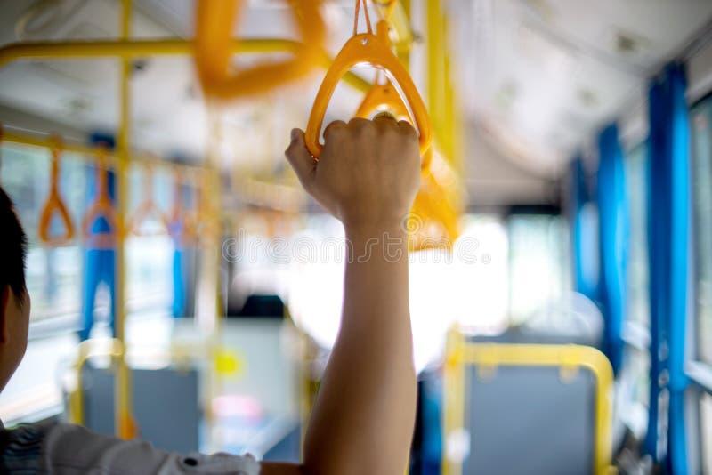 在公共汽车黄色手夹子里面的年轻人立场乘客的能举行 库存图片