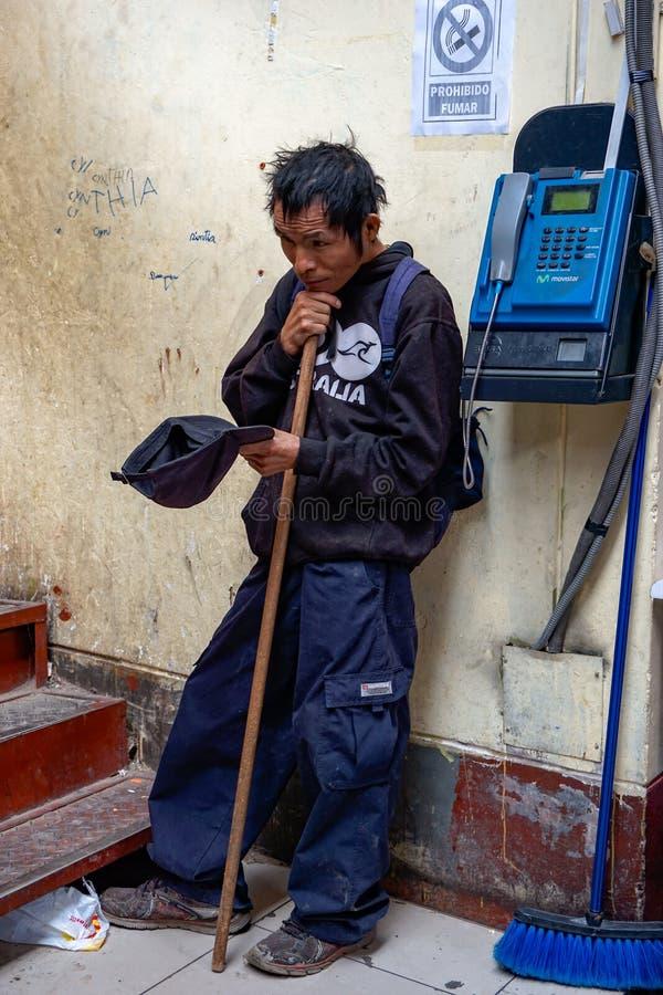 在公共电话旁边的可怜的瞎的地方印第奥叫化子乞求为施舍在瓦拉斯上市场在秘鲁 免版税库存照片
