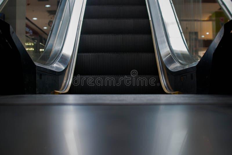 在公共购物中心,购物中心的自动扶梯 提高楼梯 电自动扶梯 由自动扶梯决定的关闭 接近的地板 免版税库存图片