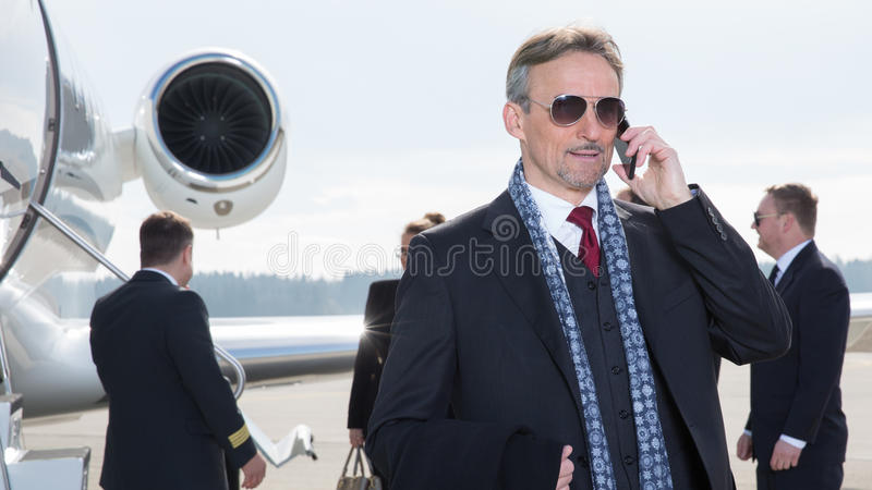 在公司喷气机前面的行政经理使用智能手机 免版税库存照片