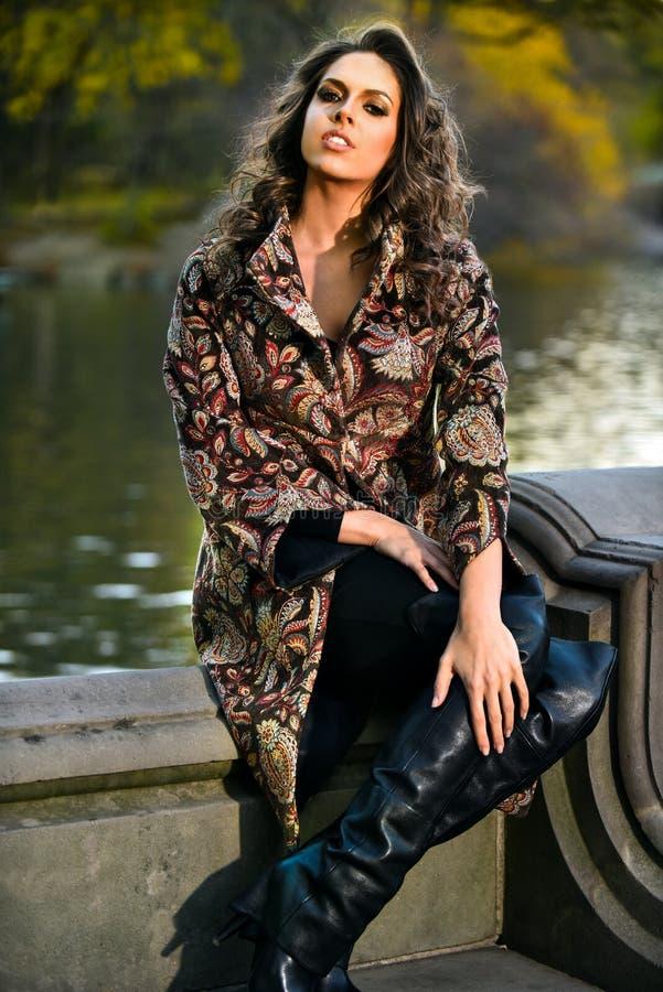 在公园塑造秋天摆在湖附近的性感的美丽的妇女室外照片  免版税图库摄影