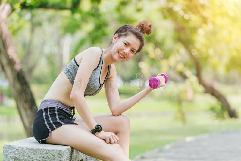 在公园室外微笑的逗人喜爱的青少年的微小的重量训练 免版税库存照片