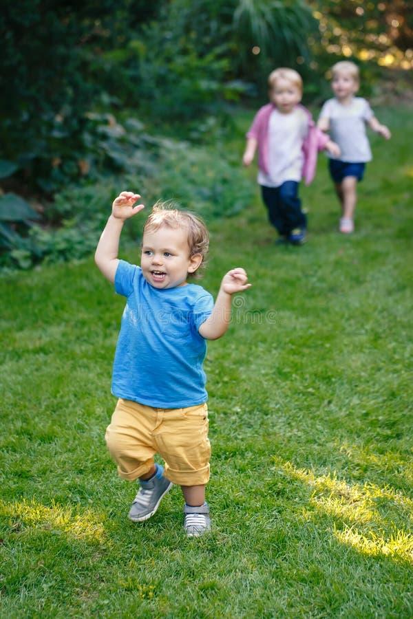 在公园庭院里编组演奏跑的三个白色白种人白肤金发的可爱的逗人喜爱的孩子画象外面 免版税库存图片