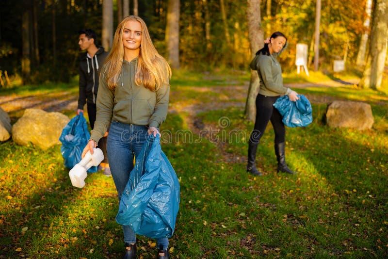 在公园捡垃圾袋的小队里年轻女志愿者 库存图片
