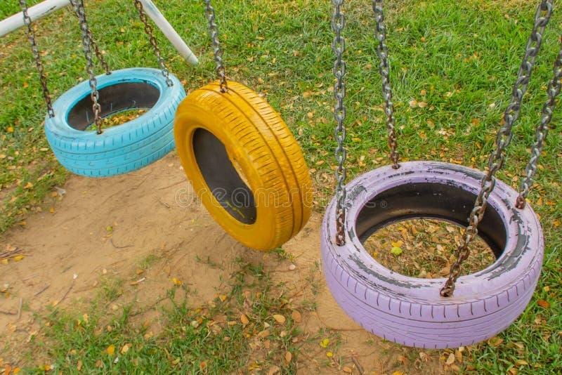 在公园摇摆由孩子的老轮胎做的椅子 免版税库存照片