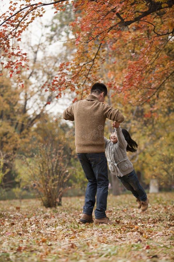在公园生摇摆的女儿在秋天 免版税库存图片