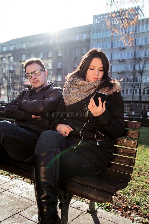 在公园的夫妇,男朋友不耐烦和使用智能手机的妇女 免版税图库摄影