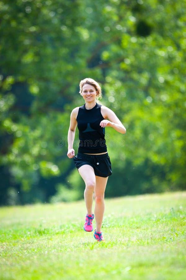 在公园的少妇奔跑 免版税库存照片