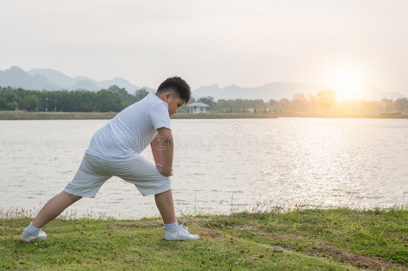 在公园的肥胖肥胖男孩锻炼在早晨 库存图片