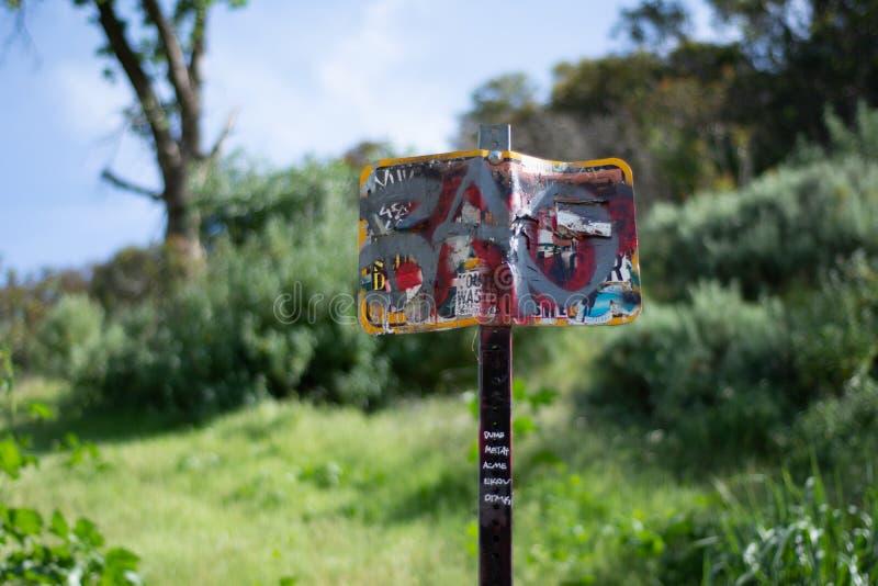 在公园的被破坏的响尾蛇警告/注意标志 免版税库存图片