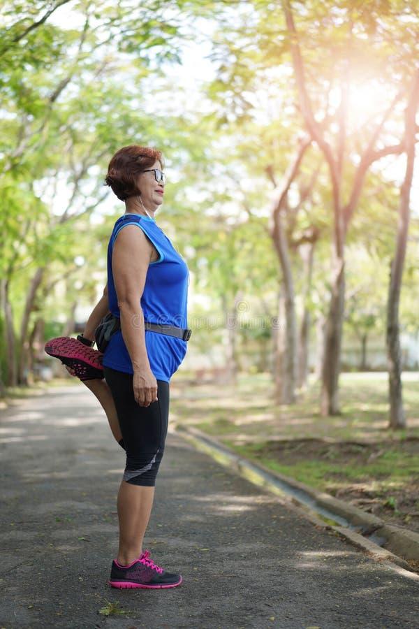 在公园的资深亚洲妇女舒展大腿肌肉 库存图片