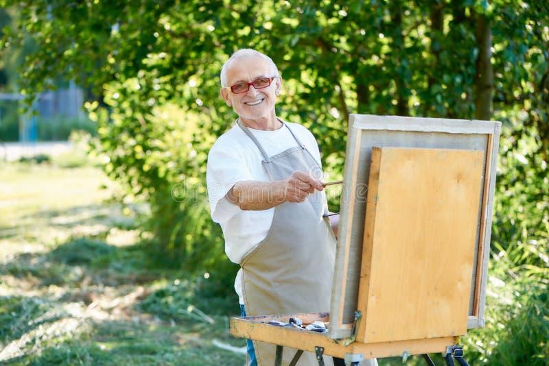 在公园的资深男性艺术家图画图片使用有油漆的调色板 库存图片