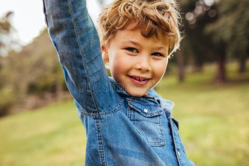 在公园的逗人喜爱的小男孩身分 免版税库存照片