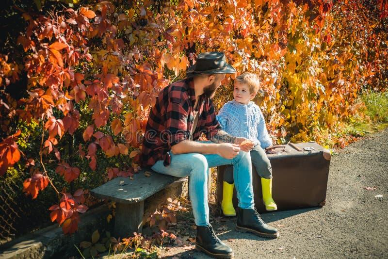 在公园的Atumn乐趣 爸爸和儿子秋天公园戏剧笑的 有他的父亲的逗人喜爱的小男孩在漫步期间 免版税库存照片