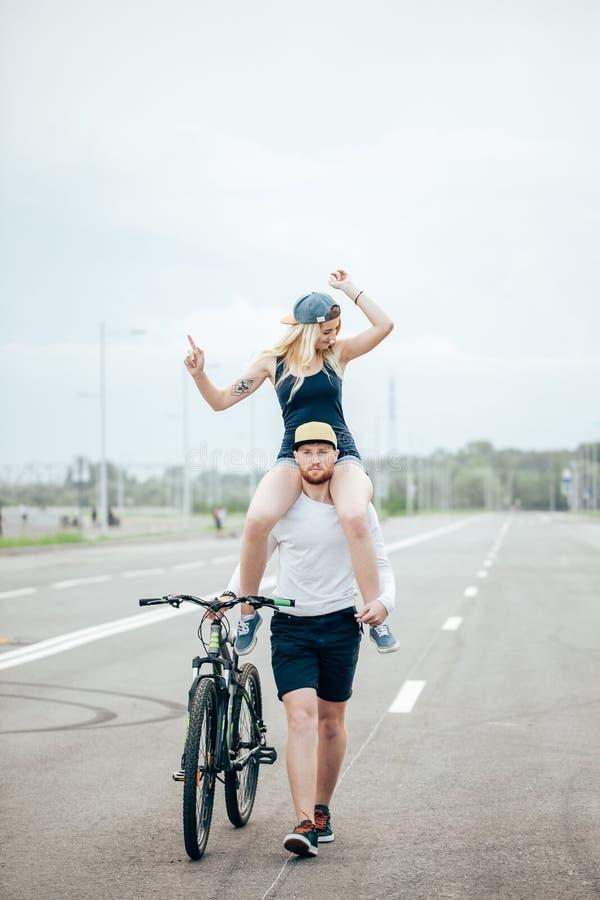 在公园结合骑自行车,肩膀的微笑和女朋友
