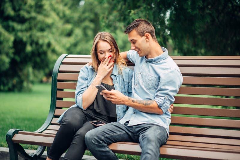 在公园给瘾,使用小配件的夫妇打电话 免版税库存图片
