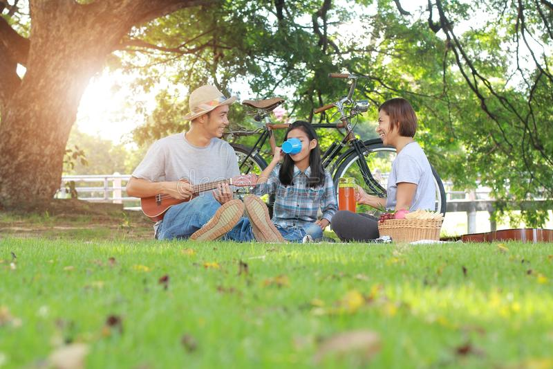 在公园统一性的愉快的亚洲家庭野餐 免版税图库摄影