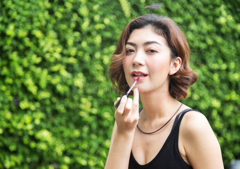 在公园背景展示的亚洲夫人用途唇膏 免版税库存照片