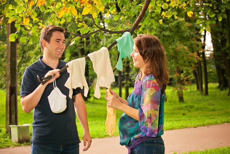 在公园藏品婴孩礼服的怀孕的夫妇 免版税图库摄影