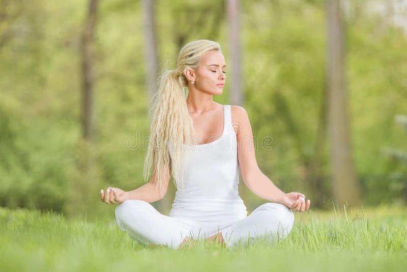 在公园里摆莲姿的瑜伽女 免版税库存照片
