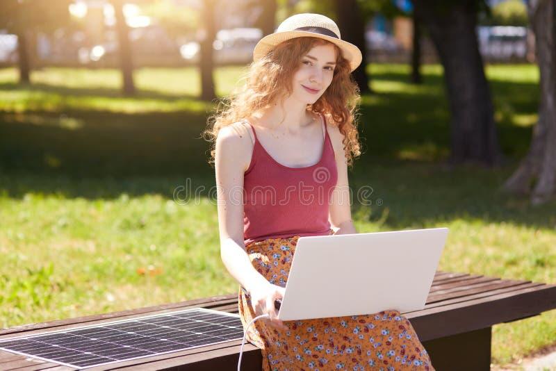 在公园长木凳的可爱的美好的女性开会,看直接地照相机,使用她的膝上型计算机,佩带的草帽,红顶 库存照片