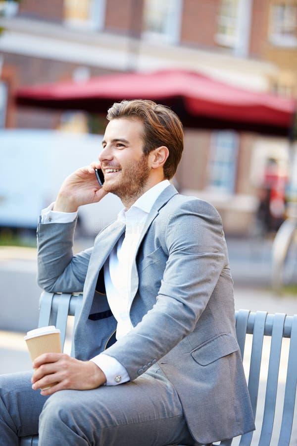 在公园长椅的商人用使用手机的咖啡 免版税库存照片
