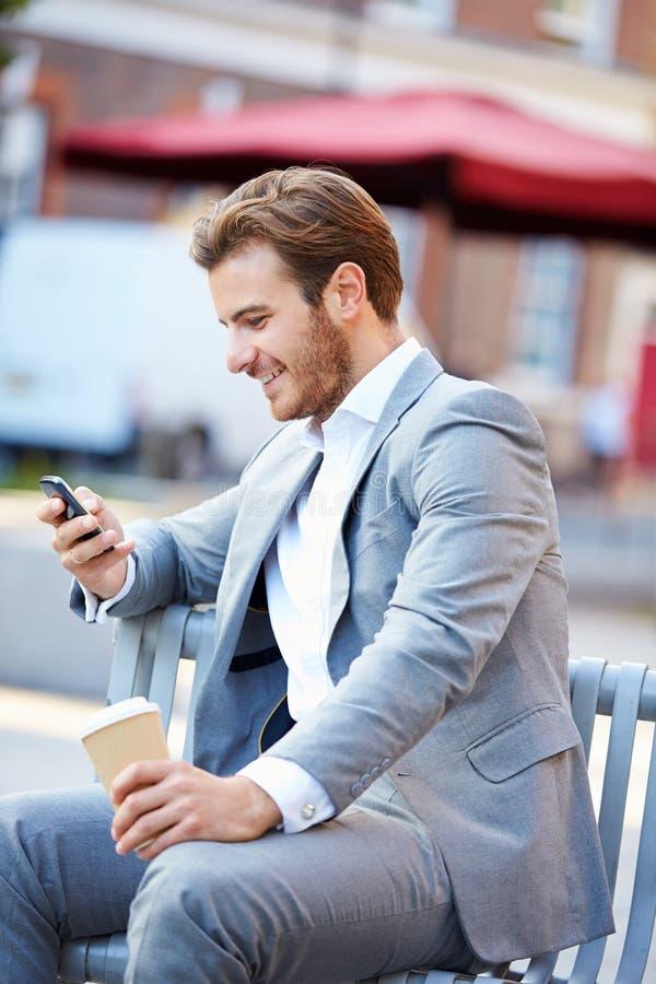 在公园长椅的商人用使用手机的咖啡 库存照片