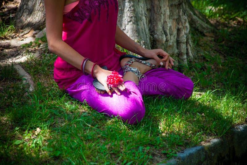 在公园降低莲花瑜伽姿势室外实践的妇女身体 免版税图库摄影