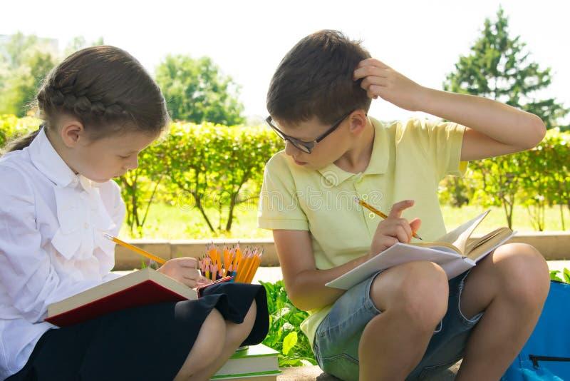 在公园,新鲜空气的,学童做他们的家庭作业,男孩偷看女孩的决定并且抓他的头 免版税库存照片