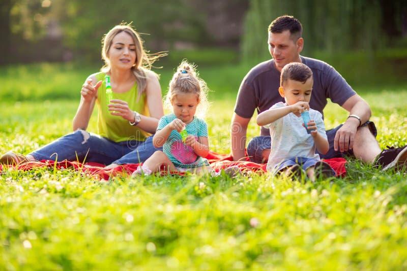 在公园-男性和女孩打击室外的肥皂泡的家庭 免版税图库摄影