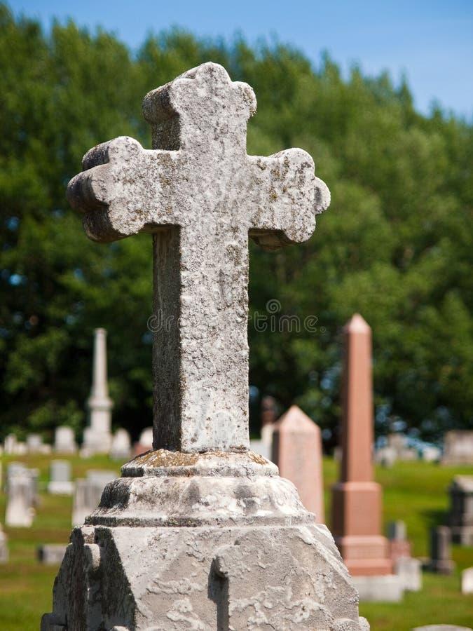 在公墓坟墓标志顶部的十字架 免版税库存图片