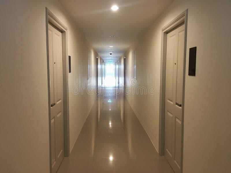 在公寓房里面的走廊有自然照明设备的通过与出口标志反射的窗口和电灯泡照明设备在地板上 免版税库存照片