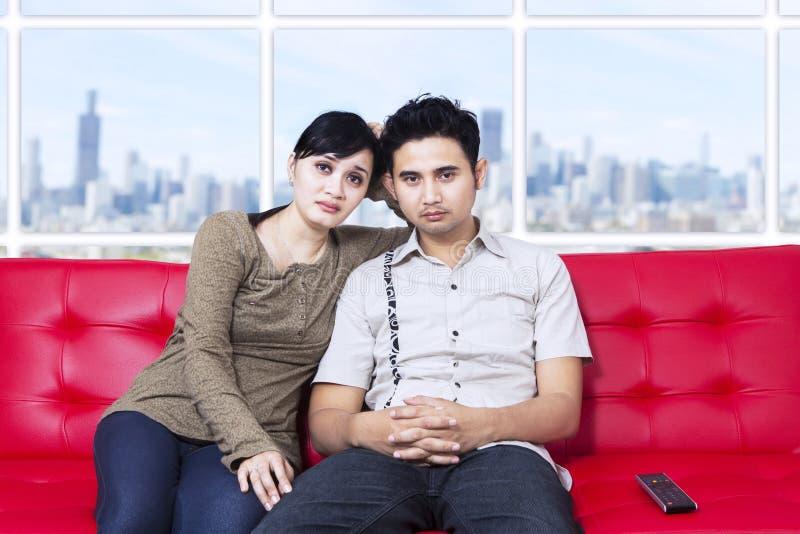 在公寓的乏味年轻夫妇观看的电视 库存照片
