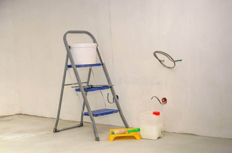 在公寓的修理 梯子和套为修理的工具 免版税库存图片