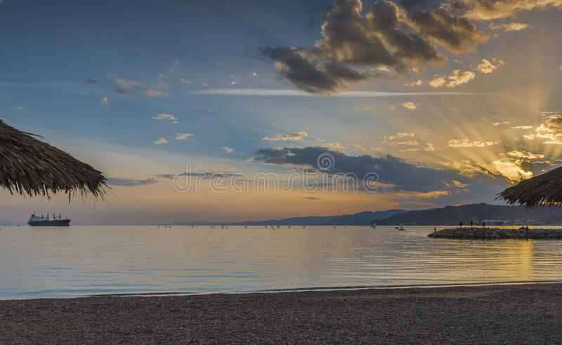 在公开海滩的日落埃拉特-著名游览城市在以色列 免版税库存照片
