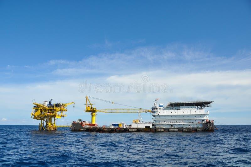 在公海闯入并且用力拖小船,在海湾的油和煤气平台或海,世界能量、近海油和船具建筑 免版税库存图片