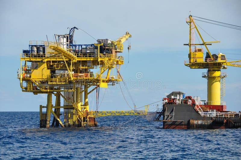 在公海闯入并且用力拖小船,在海湾的油和煤气平台或海,世界能量、近海油和船具建筑 图库摄影