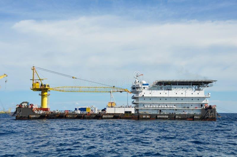在公海闯入并且用力拖小船,在海湾的油和煤气平台或海,世界能量、近海油和船具建筑 库存图片