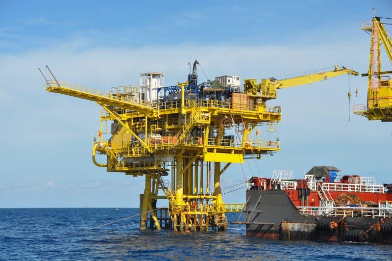 在公海闯入并且用力拖小船,在海湾的油和煤气平台或海,世界能量、近海油和船具建筑 库存照片